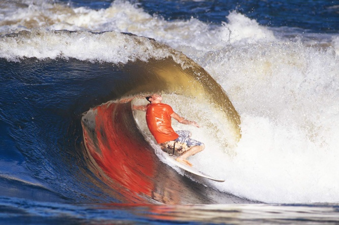 World champion skimboarder Bill Bryan performs a surfing 'layback' tube ride at Rapid 11 a few years  by Photo by Alan van Gysen